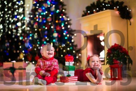 Kids Opening Christmas Presents At Fireplace Stock Photo