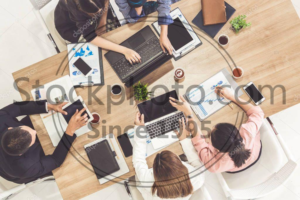 Stock photo of Business People in Group Meeting at Office Room. - Top view of businessman executive in group meeting with other businessmen and businesswomen in modern office with laptop computer, coffee and document on table. People corporate business team concept.