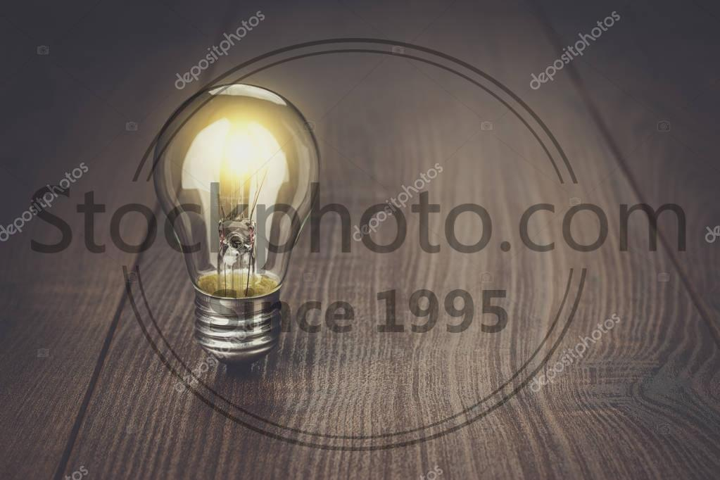 Stock photo of idea concept on wooden background - Glowing bulb standing on the brown wooden background