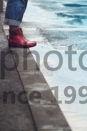 Stock photo of woman with red short boots standing on sidewalk next to a puddle - Side view closeup of young Caucasian woman feet with red short rubber boots and blue jeans standing on sidewalk next to a puddle of water after rain on a city street