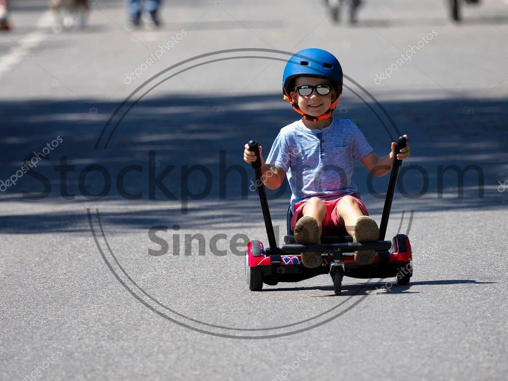 Stock photo of Happy boy standing on hoverboard or gyroscooter with kart accessory kit outdoor. New modern technologies - Happy boy standing on hoverboard or gyroscooter with kart accessory kit outdoor. New modern technologies