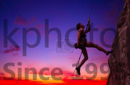 Stock photo of Climbing - Young man hanging on a rope by a rocky wall over sunset sky background