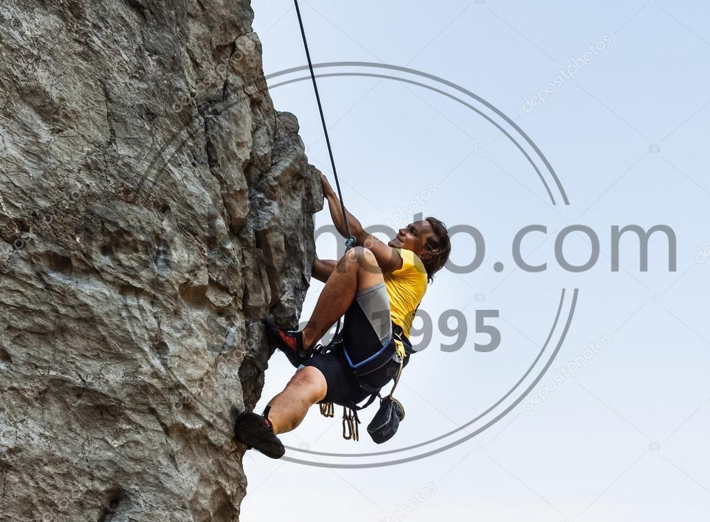 Stock photo of Man is climbing on the rock - Man is climbing on the rock with harness and rope