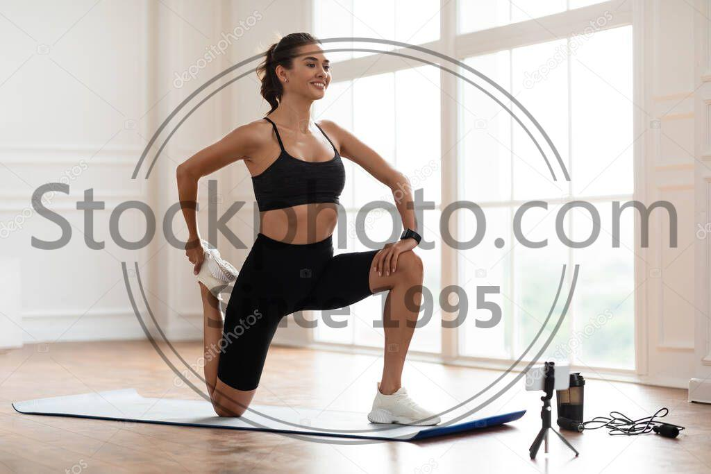Stock photo of Young woman stretching leg in front of smartphone on tripod - Smiling Sporty Woman Training At Home In Front Of Smartphone On Tripod, Beautiful Female Fitness Blogger Shooting Online Video Fitness Tutorials, Showing Stretching Legs Exercises At Camera
