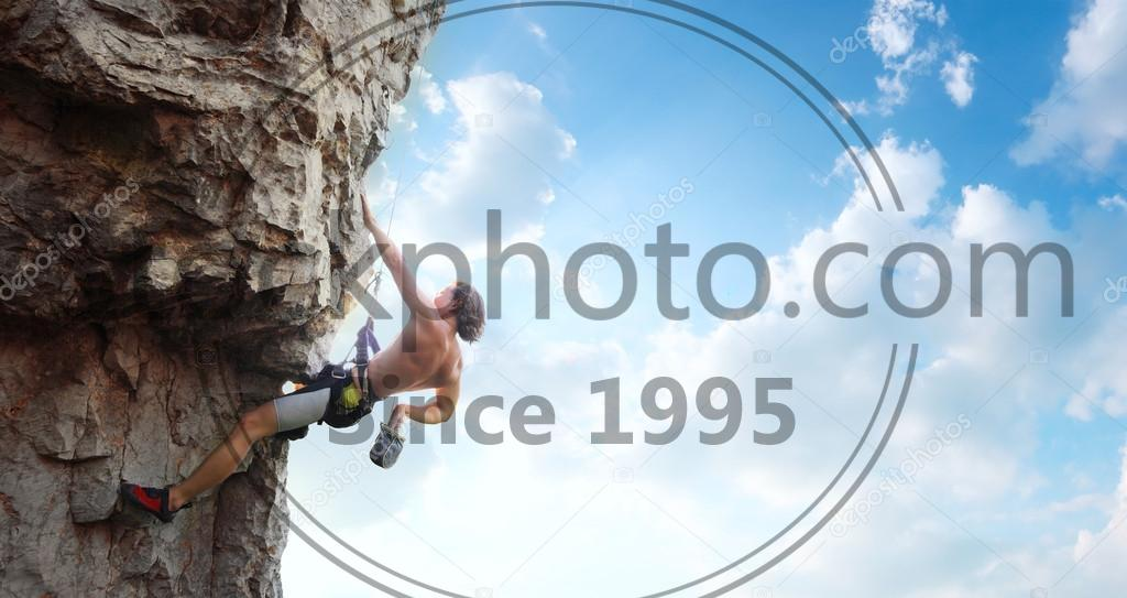 Stock photo of Climber - Young man climbing vertical wall with belay with blue cloudy sky on the background
