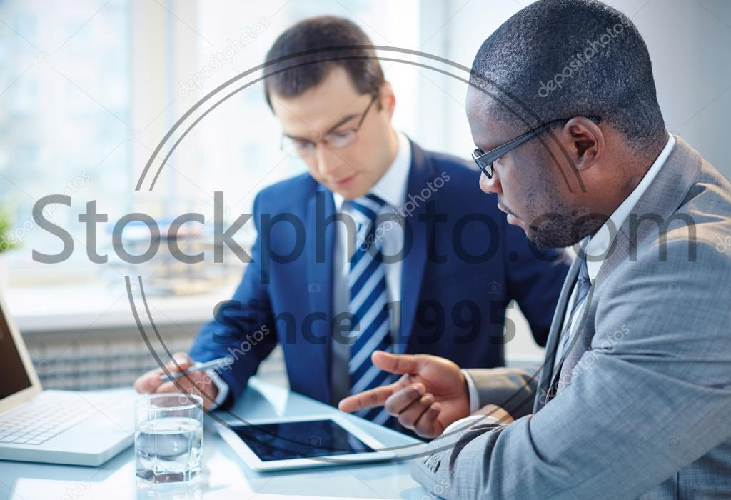 Stock photo of Businessmen discussing data - Image of two young businessmen discussing data in touchpad at meeting