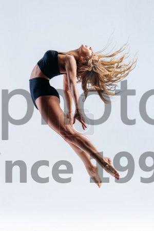 Stock photo of the dancer - Young beautiful modern style dancer posing on a studio background