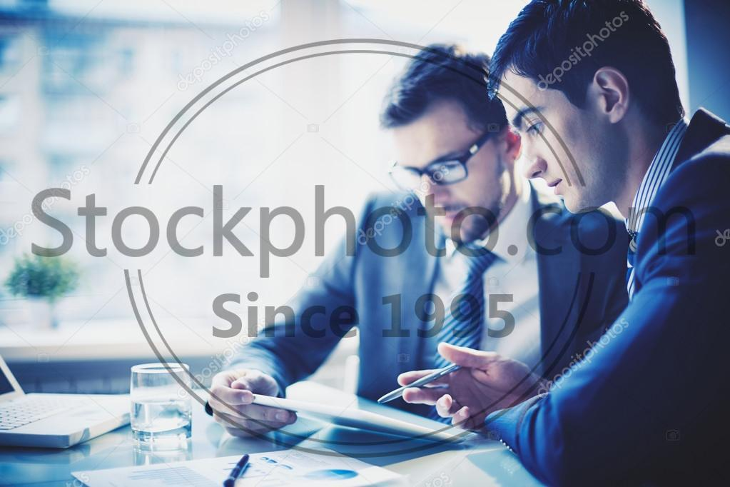 Stock photo of Businessmanex plaining idea to colleague - Image of young businessman pointing at touchpad while explaining his idea to colleague at meeting