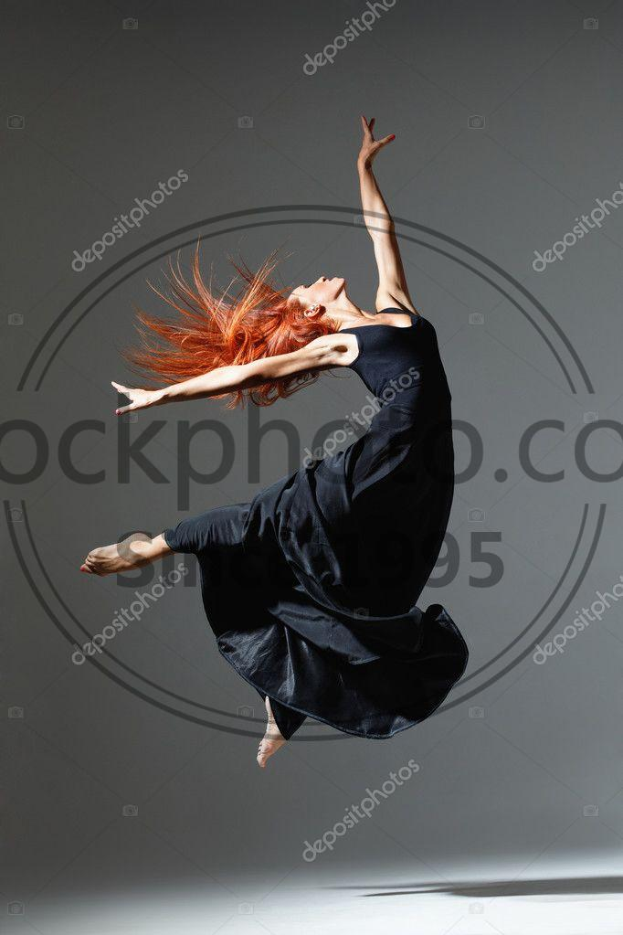 Stock photo of the dancer - Young beautiful dancer with red hair jumping on a dark studio background