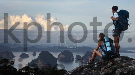Stock photo of Hikers - Two hikers with backpacks standing on top of a mountain and enjoying great view to surrounding islands