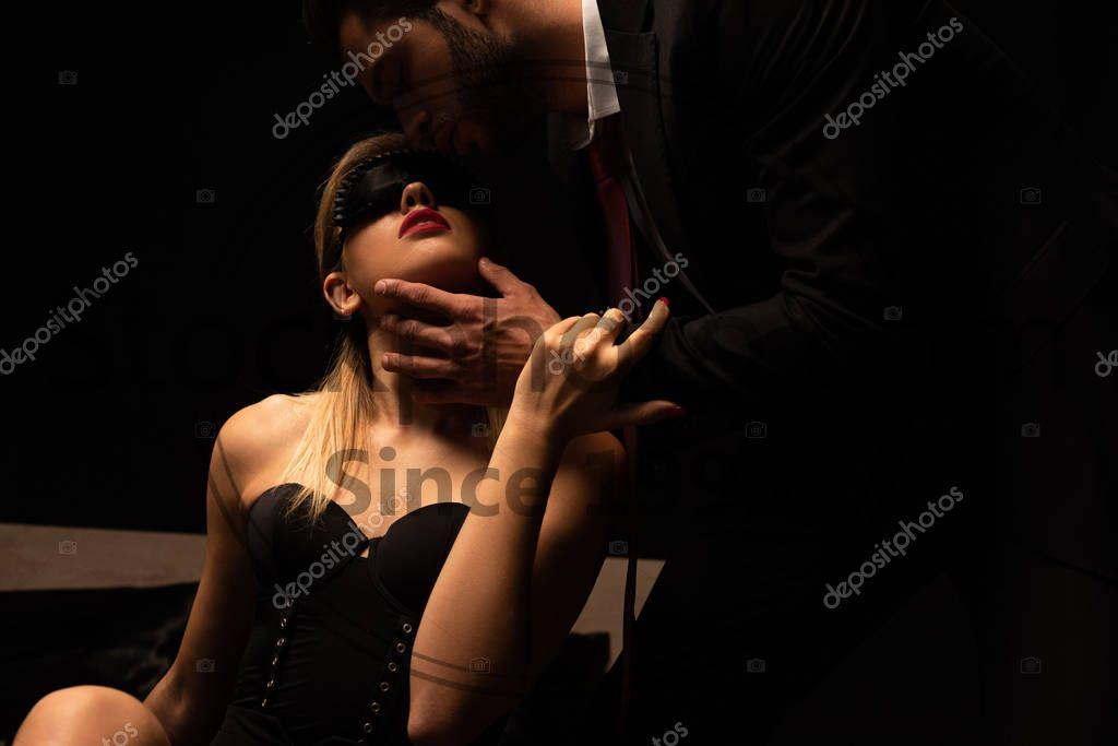 Stock photo of seductive man kissing woman in mask on bed in dark room - Seductive man kissing woman in mask on bed in dark room