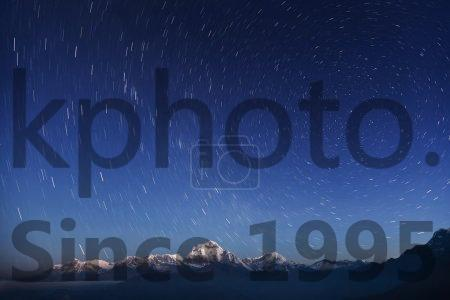 Stock photo of Night laconic landscape - Starry sky over the snowy mountains.