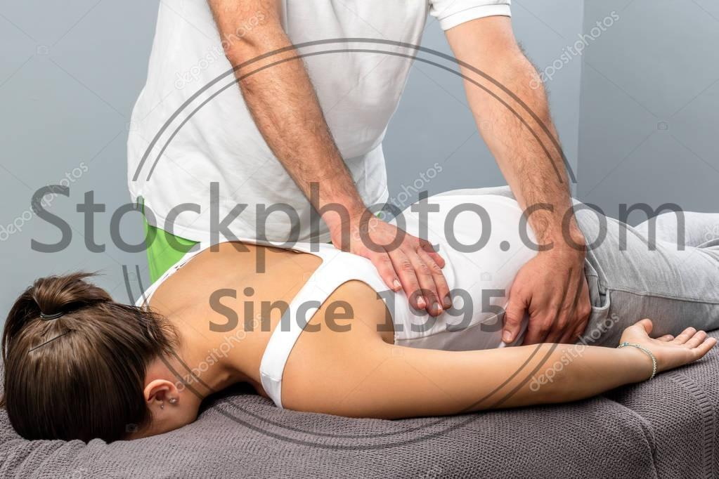 Stock photo of Physiotherapist doing massage on female lower back. - Close up of male osteopath doing manipulative massage on female lower back.