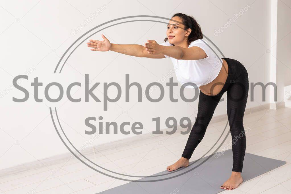 Stock photo of Young flexible pregnant woman doing gymnastics on rug on the floor on white background. The concept of preparing the body for easy childbirth - Young flexible pregnant woman doing gymnastics on rug on the floor on white background. Preparing the body for easy childbirth