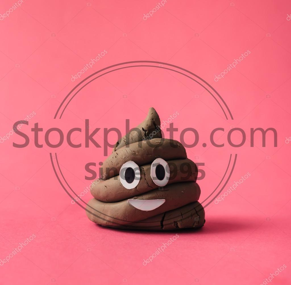 Stock photo of Funny poop emoticon - Poop emoticon on pink background.