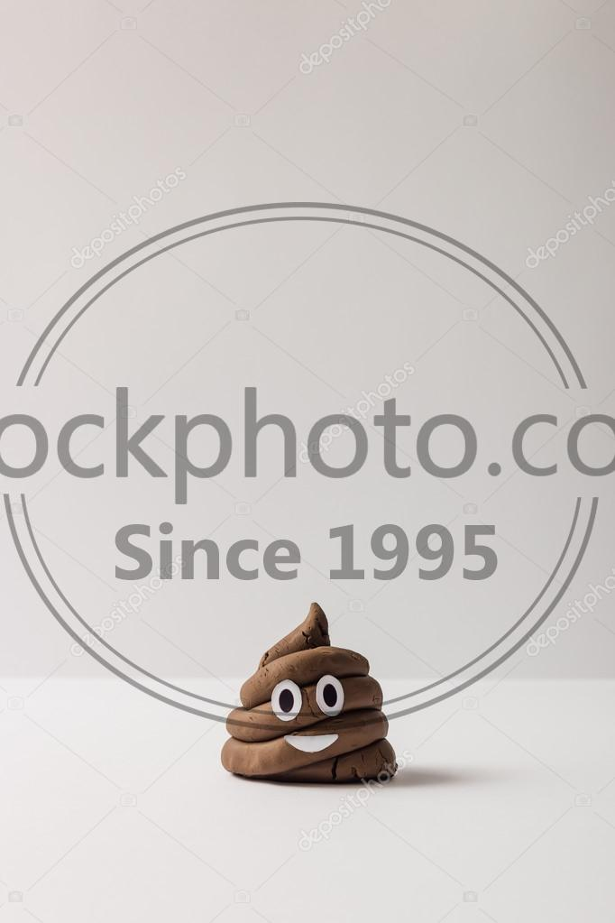 Stock photo of Funny poop emoticon - Poop emoticon on bright background. Minimal concept.