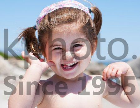 Stock photo of Little girl smiling - Little girl  smiling on beach with her hands up