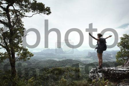 Stock photo of Backpacker - Young hiker with backpack standing with raised hands on a cliff's edge and looking over wild tropical valley