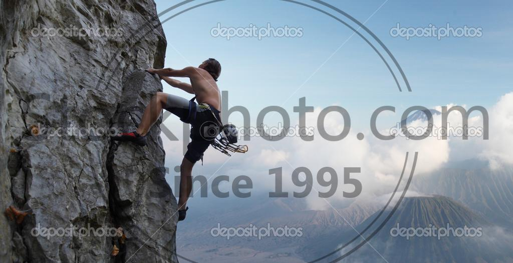 Stock photo of Climber - Young man climbing natural rocky wall with volcanoes on the background