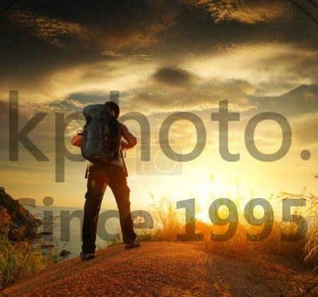 Stock photo of Hiker - Hiker with backpack standing on a rock and enjoying sunset over sea
