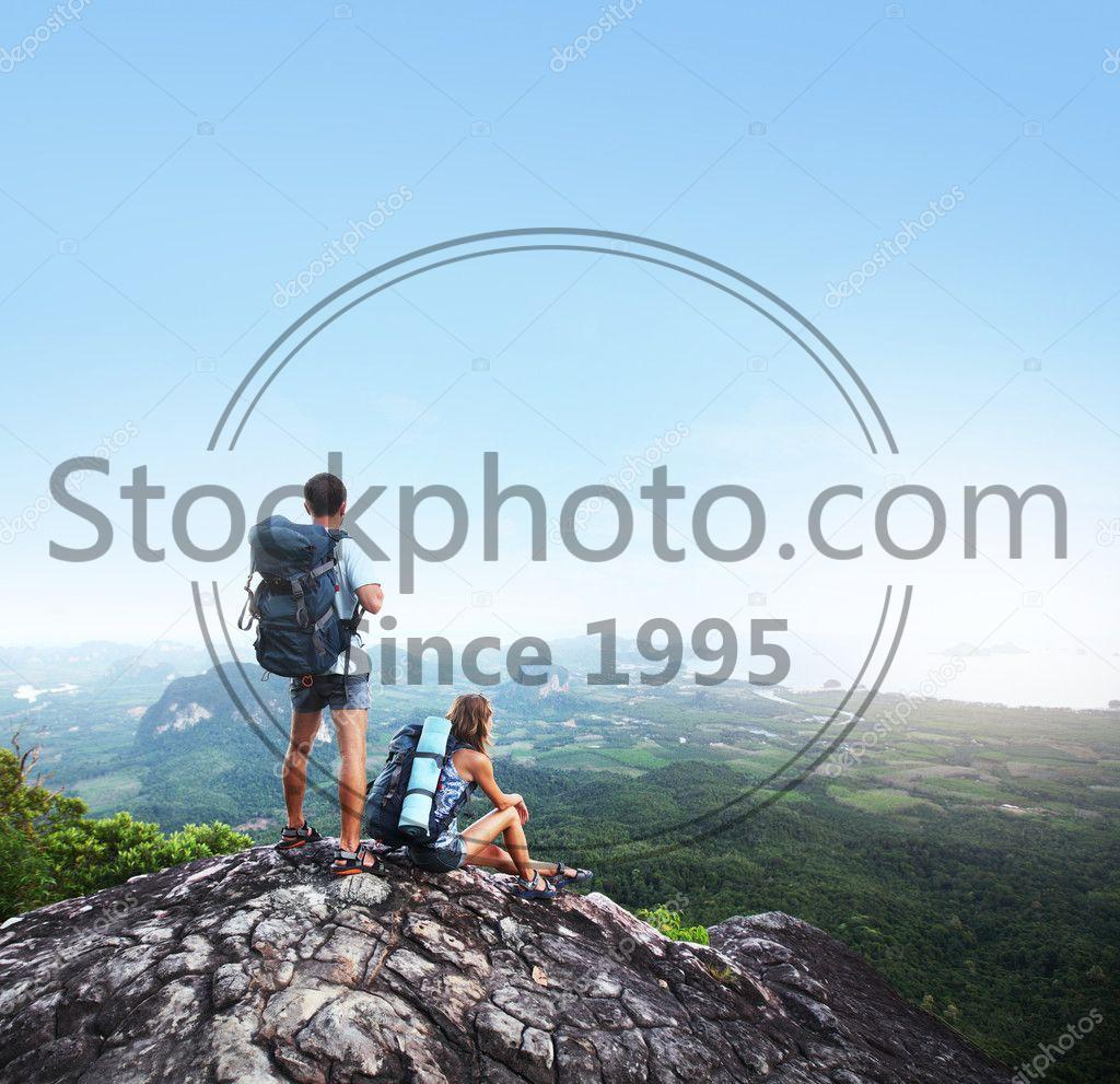 Stock photo of Backpackers - Hikers with backpacks standing on top of a mountain and enjoying a valley view