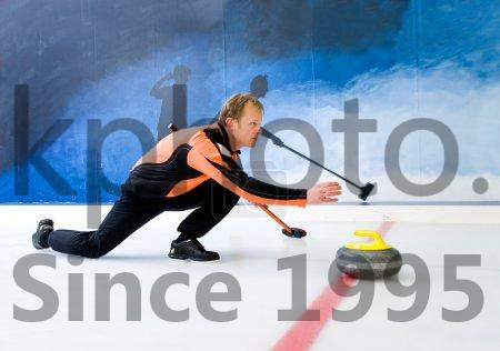 Stock photo of Curling - Curling player delivering a stone on a curling rink, sliding over the ice
