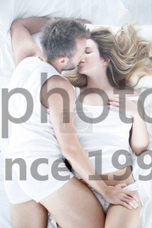 Stock photo of Husband kissing and touching wife - Picture of husband kissing and touching his beautiful wife