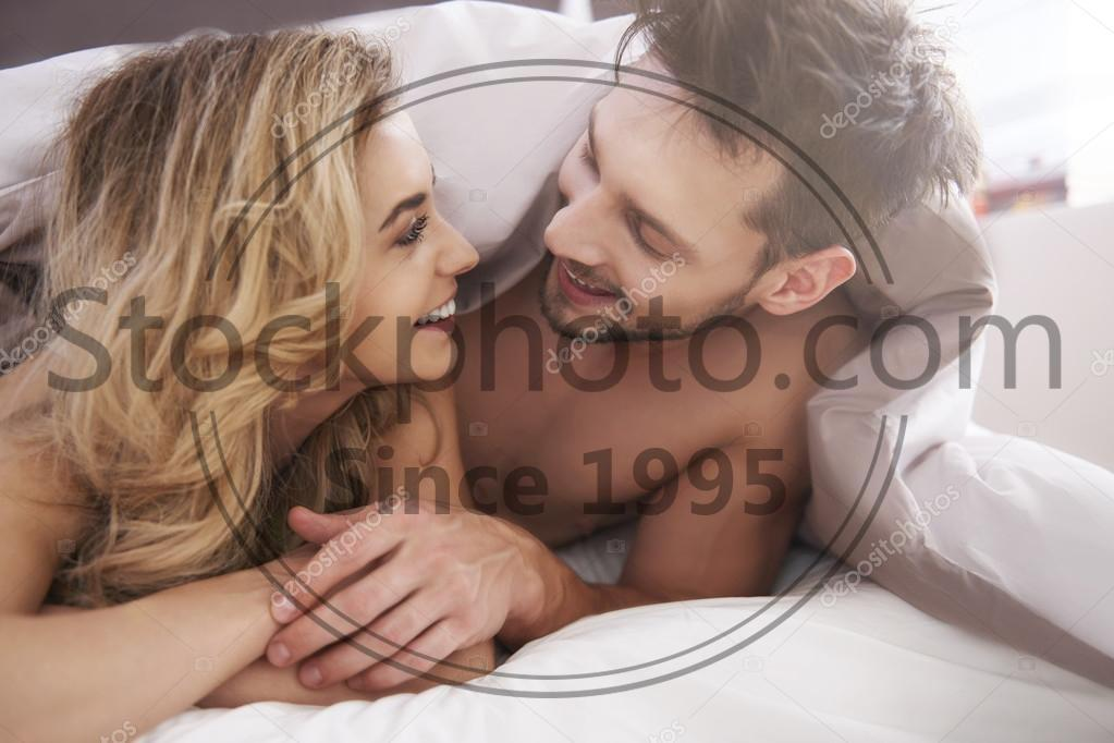 Stock photo of Charming couple covered with a duvet - Charming couple covered with a duvet