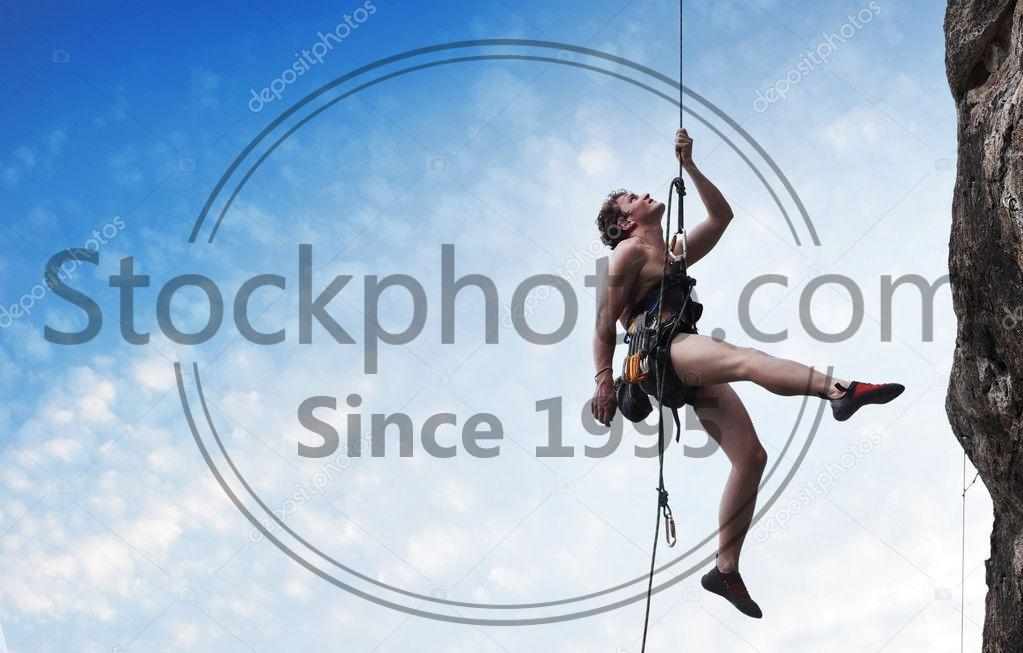 Stock photo of Climber - Young male climber hanging on a rope and looking to somewhere on blue cloudy sky background