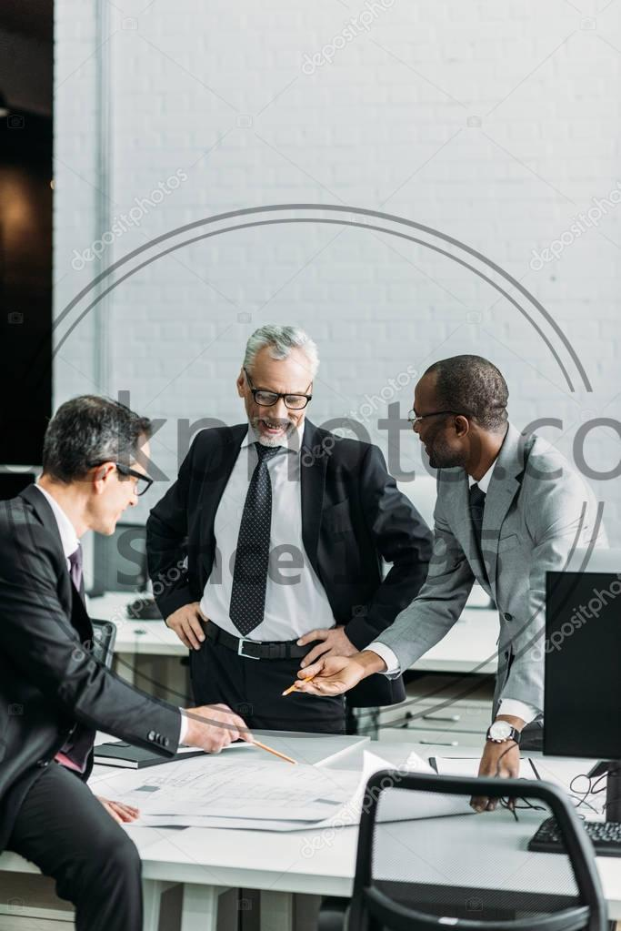 Stock photo of multiethnic businessmen discussing new business strategy on meeting in office - Multiethnic businessmen discussing new business strategy on meeting in office