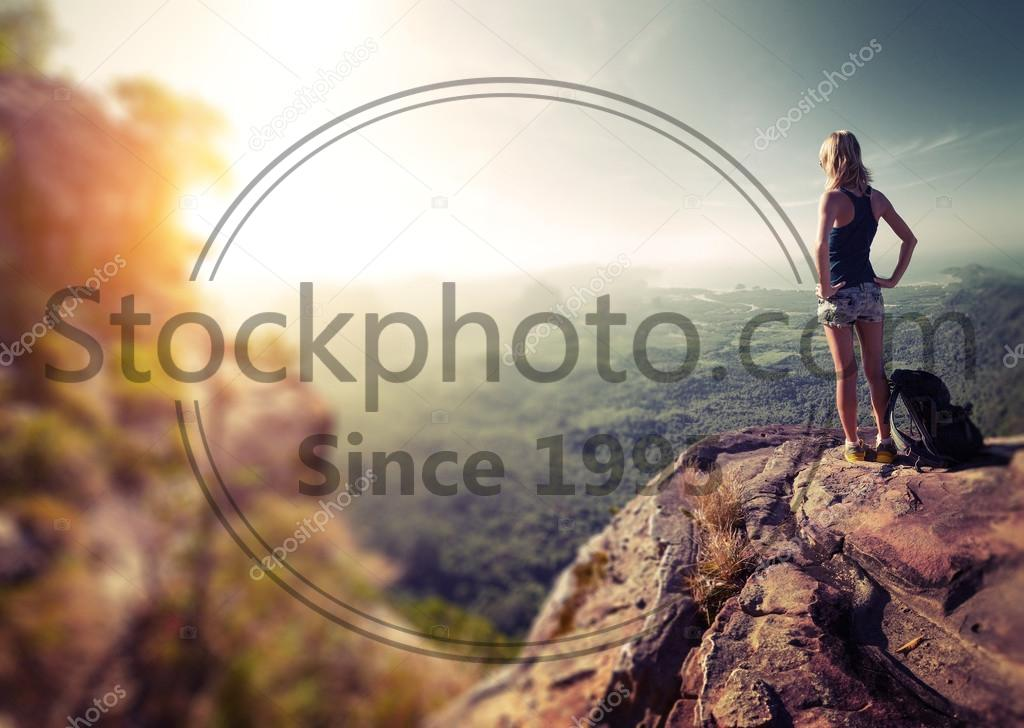 Stock photo of Hiker lady - Hiker with backpack standing on top of the mountain and enjoying valley view at sunrise. Edges are blurred