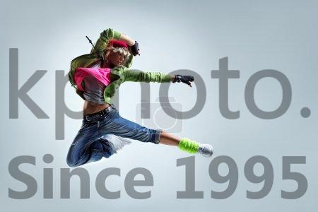 Stock photo of Cool jump - Hip-hop dancer jumping on a studio background