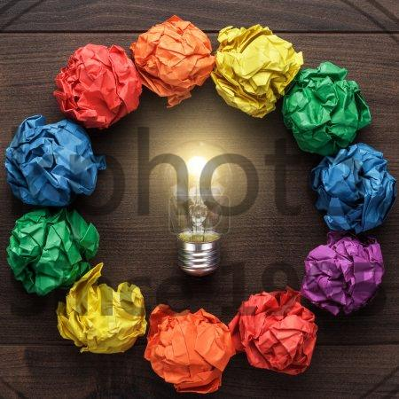 Stock photo of best idea concept with crumpled colorful paper circle - Best idea concept with crumpled colorful paper circle and light bulb in the centre on wooden table