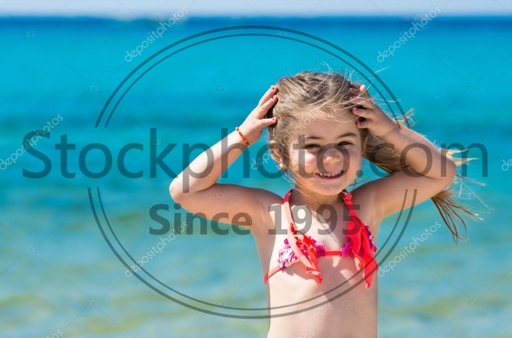 Stock photo of Adorable happy smiling little girl on beach vacation - Adorable happy smiling little girl on beach vacation, tropical sea background