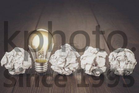 Stock photo of great idea concept - Great idea concept with crumpled office paper and light bulb standing on the table