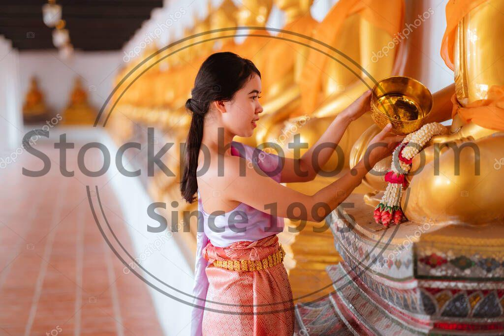 Stock photo of Asian woman wearing a Thai national costume bathing of buddha during the Songkran Festival in Thailand. Thai New Year's Day. Thai tradition. - Asian woman wearing a Thai national costume bathing of buddha during the Songkran Festival in Thailand. Thai New Year's Day. Thai tradition.