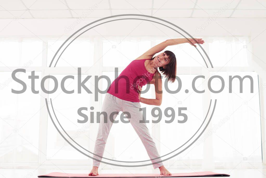 Stock photo of Excited model standing side stretch in the gym  - Low angle of excited woman standing side stretch in the gym. Open position and inducing feelings of calm. Standing supported side stretch