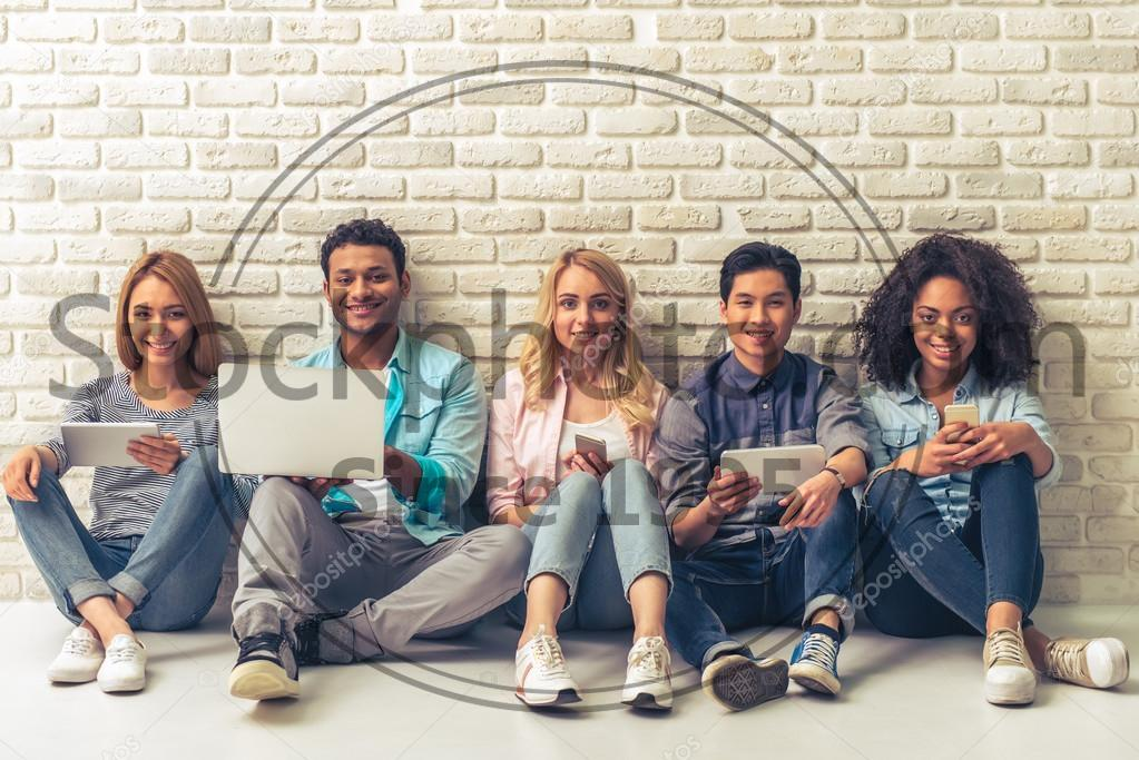 Stock photo of Young people with gadgets - Beautiful young people of different nationalities are using gadgets, looking at camera and smiling, sitting against white brick wall