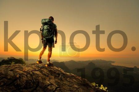 Stock photo of Hiker - Hiker with backpack standing on top of a mountain and enjoying sunrise