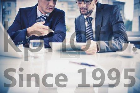 Stock photo of Discussion - Image of two young businessmen discussing document in touchpad at meeting