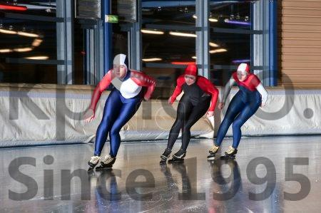 Stock photo of Three speed skaters - Three speed skaters making their laps on an indoor ice rink