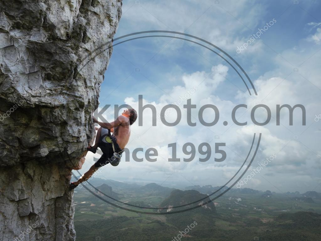 Stock photo of Climber - Young man climbing natural rocky wall with tropical valley on the background