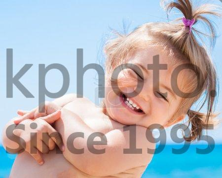 Stock photo of Adorable happy smiling little girl on beach vacation - Little girl smiling in a tropical beach, clear and tropical sea on background
