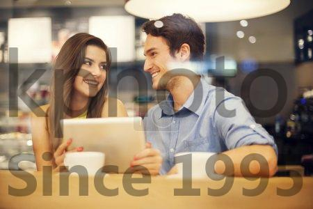 Stock photo of Romantic date in cafe - Flirting couple in cafe using digital tablet