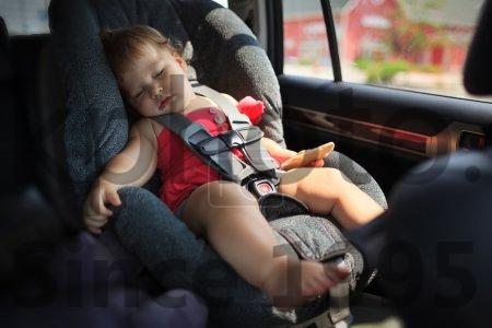 Stock photo of Child sleeping in car - Toddler girl sleeping in child car seat.