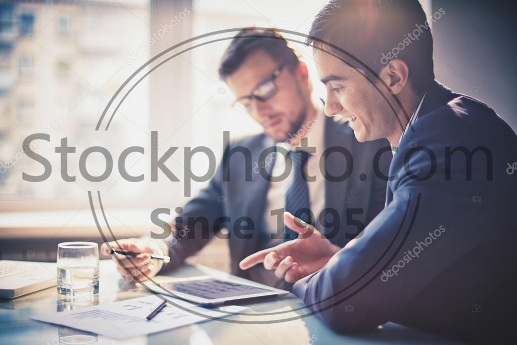 Stock photo of Businessmen using touchpad - Image of two young businessmen using touchpad at meeting