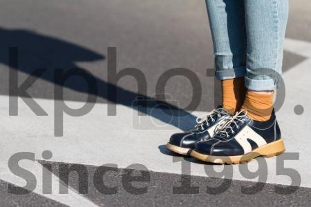 Stock photo of close up of woman shoes standing on the street - Side view close up of a fashionable young woman wearing black shoes and blue jeans standing on a street natural light