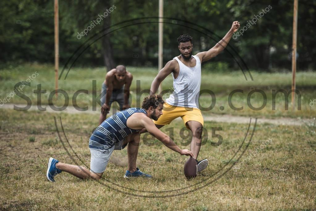 Stock photo of multicultural men playing football - Group of young multicultural men playing football on court