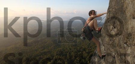 Stock photo of Climbing - Young man climbs on a rocky wall in a valley with mountains