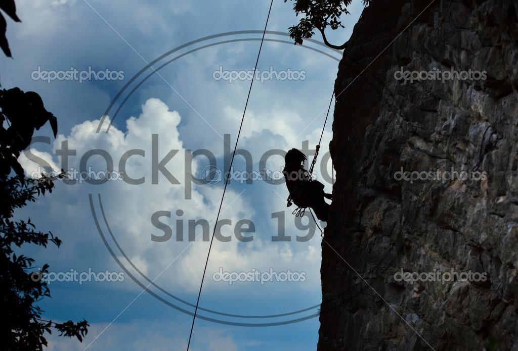 Stock photo of Climber - Silhouette of a climber hanging on a rope by cliff with blue stormy clouds on the background